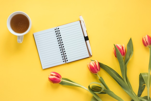 Notizbuch nahe schale getränk und frischen tulpen mit grünen blättern