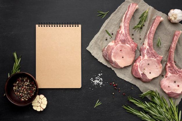 Notizbuch neben rohem fleisch auf backpapier