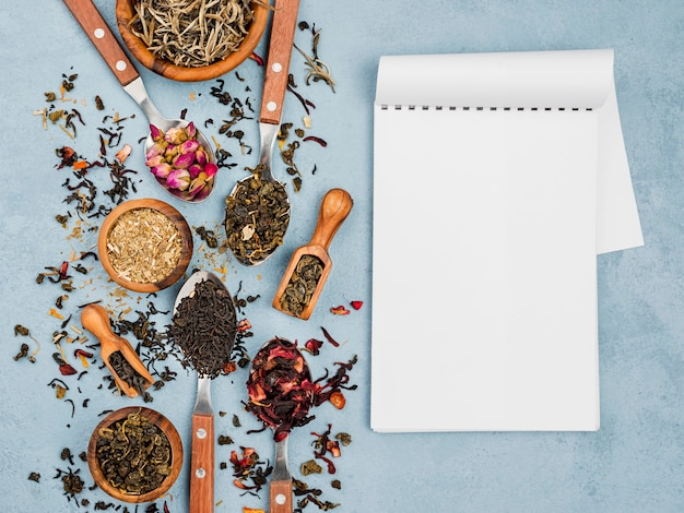 Notizbuch neben schaufel und schalen mit kräutertee