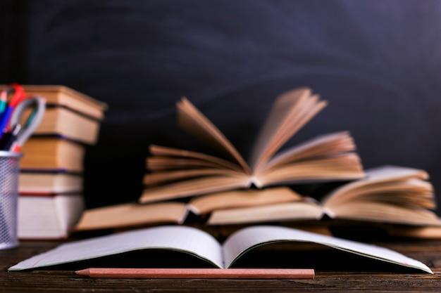 Notizbuch, offene bücher und schulbedarf auf einem dunklen holztisch vor dem hintergrund eines kreidebrettes