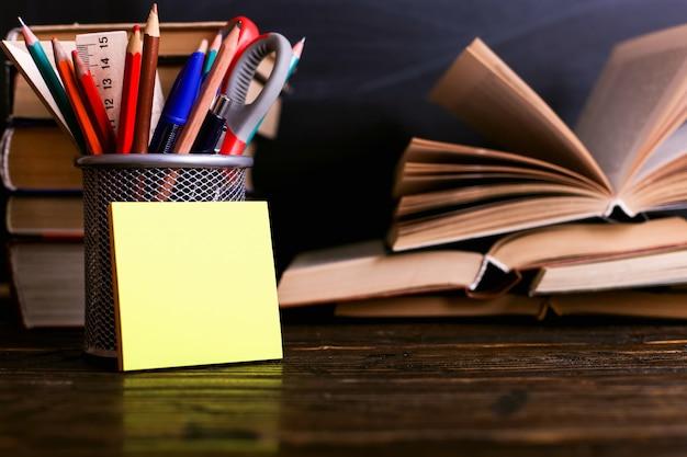Notizbuch, offene bücher und stand für stifte auf einem dunklen holztisch auf dem hintergrund des kreidebrettes