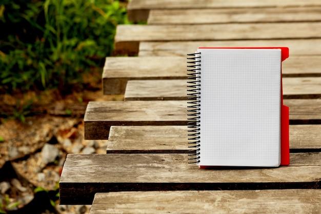 Notizbuch, offener notizblock auf einer spirale auf einem dunklen holz strukturiert