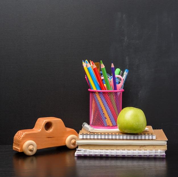 Notizbuch, rosa briefpapierglas mit mehrfarbigen holzstiften auf dem hintergrund einer leeren schwarzen kreidetafel, zurück zum schulkonzept