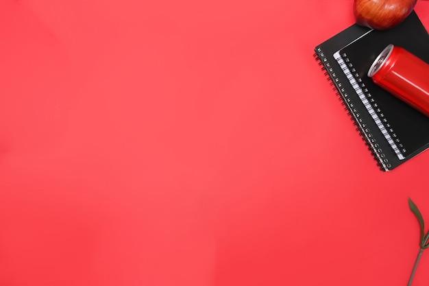 Notizbuch, rote dose und apfel auf rotem grund. platz kopieren.