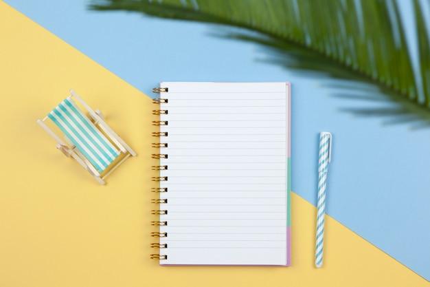 Notizbuch, stift, liegestuhl auf zweifarbigem hintergrund gelb und blau, kopierraum, flache lage. arbeitsbereich des freiberuflers, draufsicht. freiberuflich tätig, urlaubsplanung, reise-, verkaufskonzept. horizontal