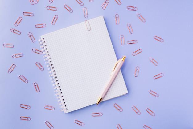 Notizbuch, stift und büroklammern. weiblicher satz blauer hintergrund. selektiver fokus