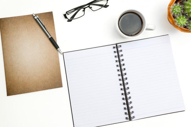 Notizbuch, stift und gläser der draufsicht leeres auf weißem schreibtisch