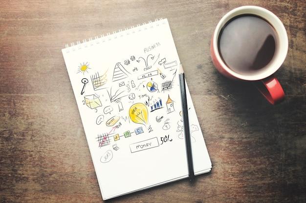 Notizbuch, stift und tee auf holztisch
