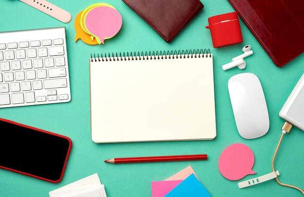 Notizbuch, tastatur, power bank mit kabel, rotes smartphone mit leerem schwarzen leeren bildschirm