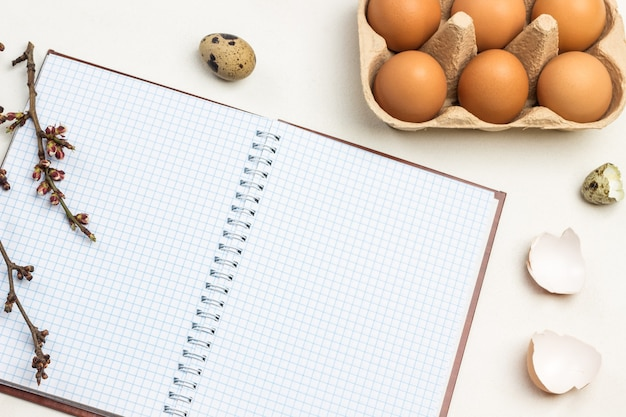 Notizbuch über federn. braune hühnereier im kartonbehälter. ast des baumes auf notizbuch. wachtelei und eierschalen auf dem tisch. draufsicht.