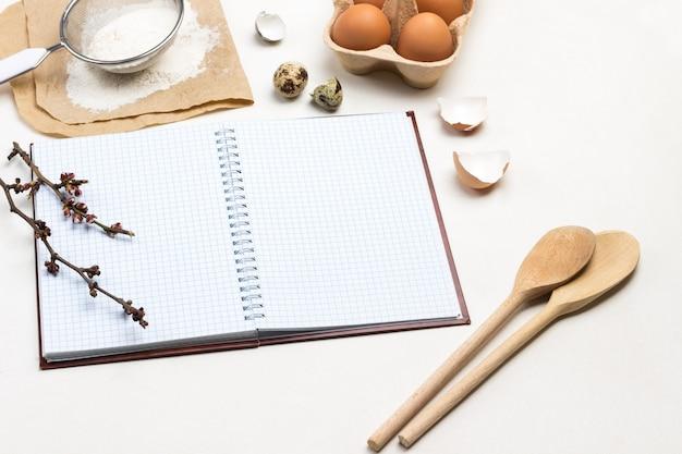 Notizbuch über federn. zwei holzlöffel. hühnereier und hühnerschalen. mehl und sieb auf papier. weißer hintergrund. draufsicht.