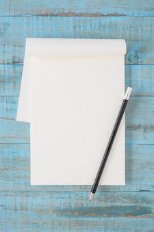 Notizbuch und bleistift auf blauem holz tisch