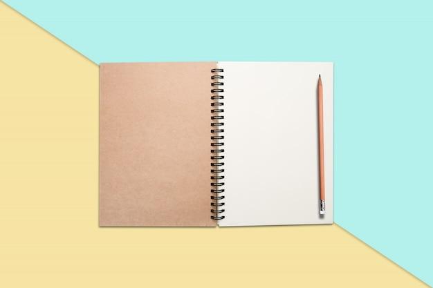 Notizbuch und bleistift auf farbigem hintergrund