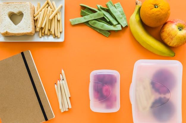 Notizbuch und bleistifte nahe lunchboxen und gesundem lebensmittel