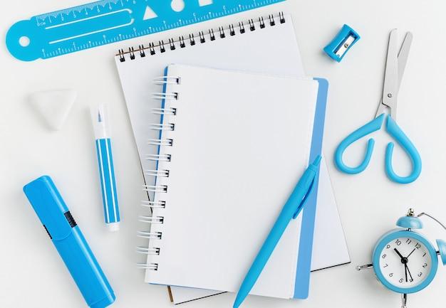 Notizbuch und briefpapier auf weißem desktop. bildungskonzept. modell direkt darüber.