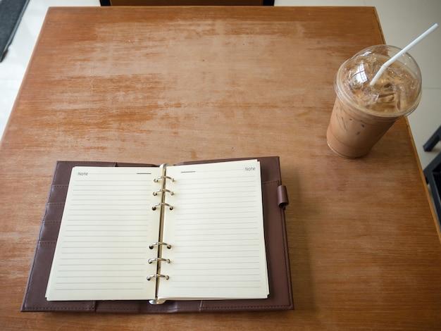 Notizbuch- und eiskaffee auf hölzernem hintergrund