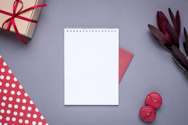 Notizbuch und geschenk im kasten mit satinband auf grau
