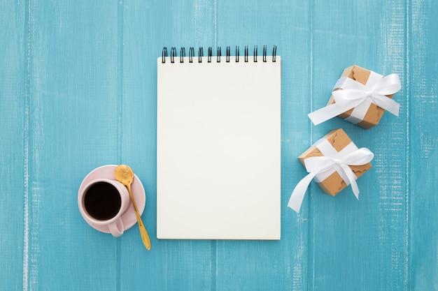 Notizbuch und geschenkboxen mit kaffee auf einem blauen hölzernen