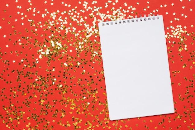 Notizbuch und goldene sternkonfettis, weihnachten und konzept des neuen jahres