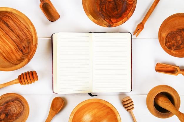 Notizbuch und hölzernes gerät in der küche auf weißem hölzernem hintergrund mit kopienraum.