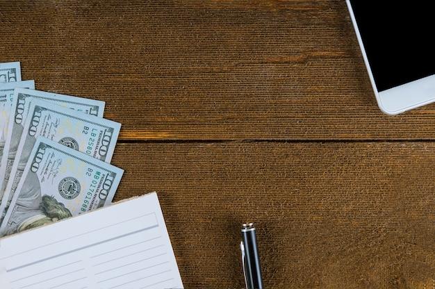 Notizbuch und intelligentes telefon der dollar auf holz