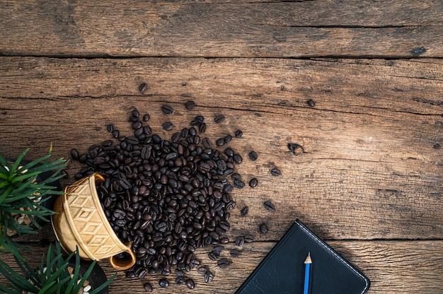 Notizbuch und kaffeebohnen werden auf den schreibtisch gelegt
