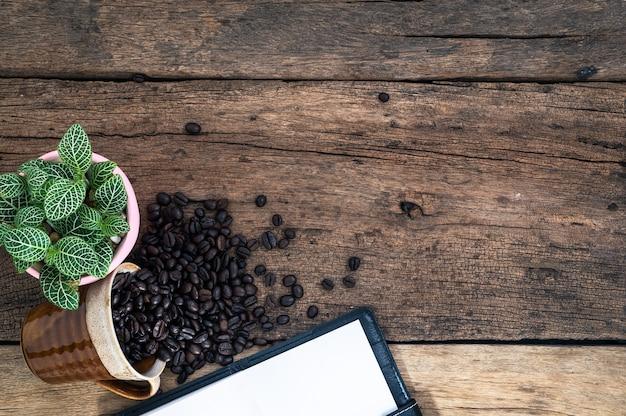 Notizbuch und kaffeebohnen werden in der draufsicht platziert