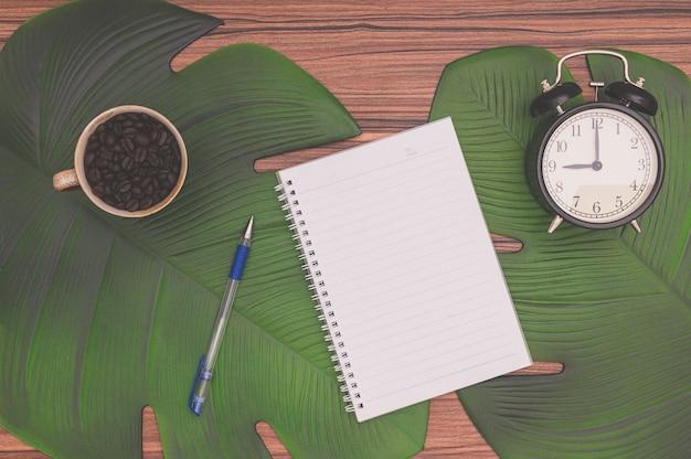 Notizbuch und kaffeetasse auf dem schreibtisch