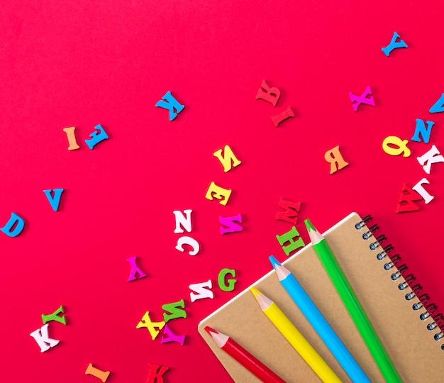 Notizbuch und mehrfarbige hölzerne bleistifte auf einem roten hintergrund