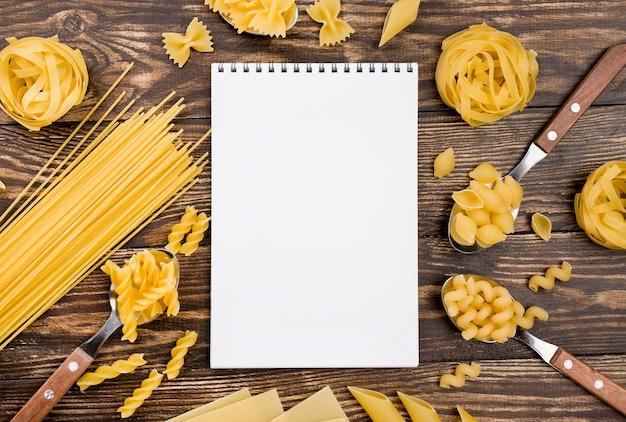 Notizbuch und nudeln in löffeln