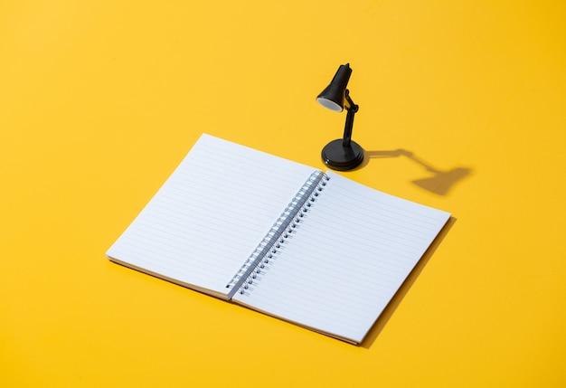 Notizbuch und schwarze kleine lampe auf gelber oberfläche