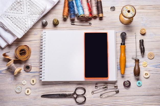 Notizbuch und smartphone auf hölzernem hintergrund, handwerksthema.
