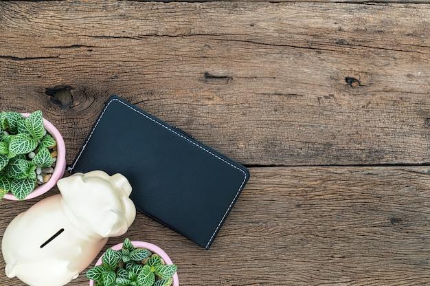Notizbuch und sparschwein liegen auf dem schreibtisch