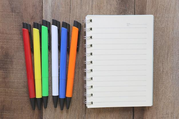 Notizbuch und stift auf altem holz für den designhintergrund.
