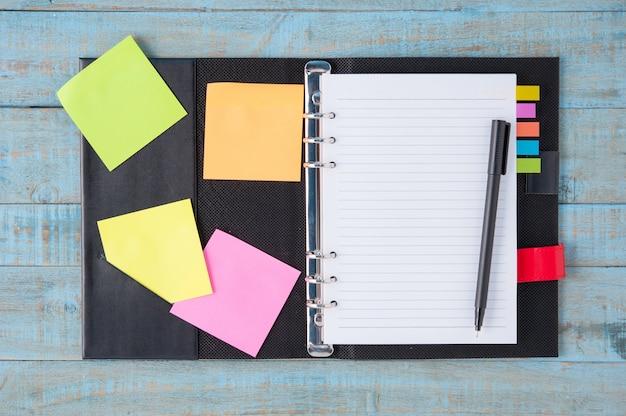 Notizbuch und stift auf blauem holz tisch