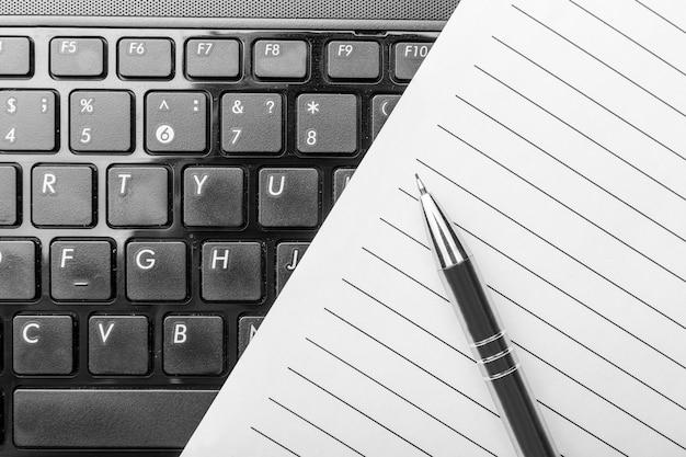 Notizbuch und stift auf der schwarzen tastatur