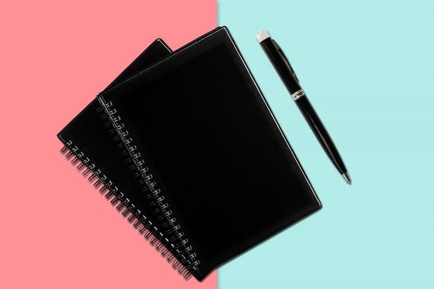 Notizbuch und stift auf farbigem hintergrund
