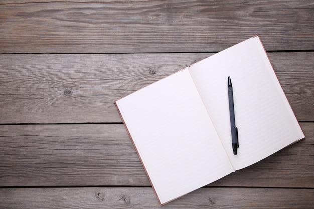 Notizbuch und stift auf grauem hölzernem hintergrund