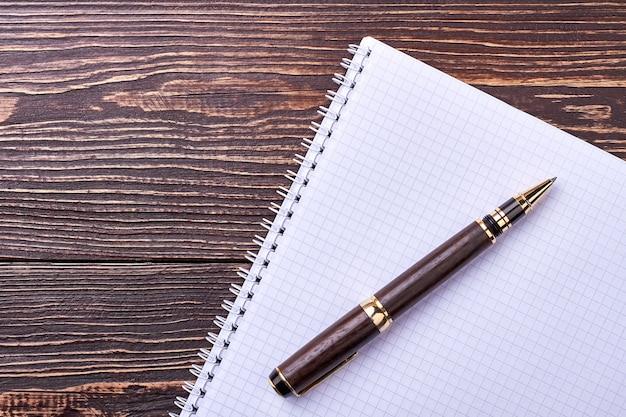 Notizbuch und stift auf holz. papiernotizblock auf holzoberfläche. drücken sie sich schriftlich aus.