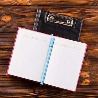 Notizbuch und stift auf klemmbrett