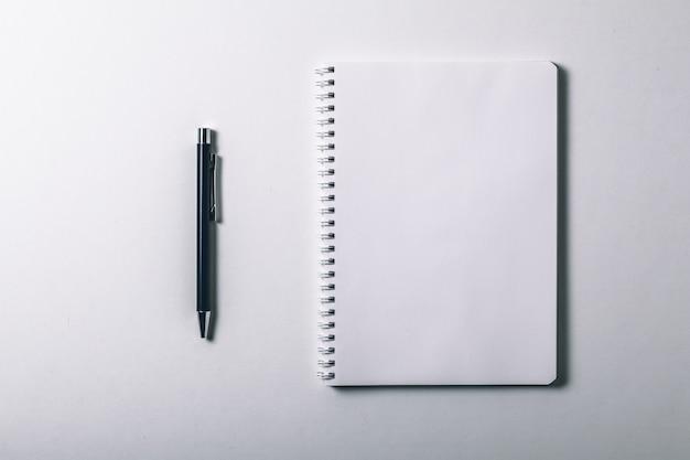 Notizbuch und stift auf weißem hintergrund.