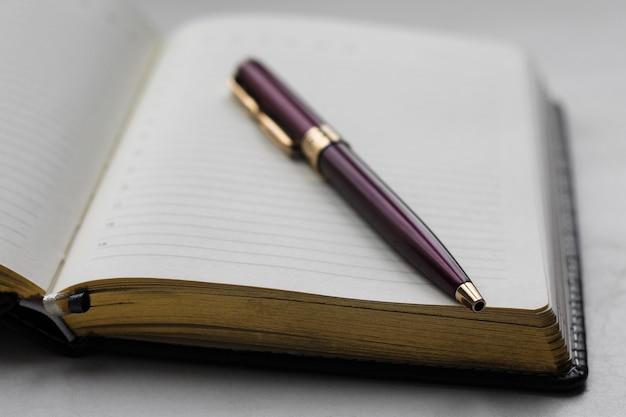 Notizbuch und stift hautnah. büro geschäftskonzept