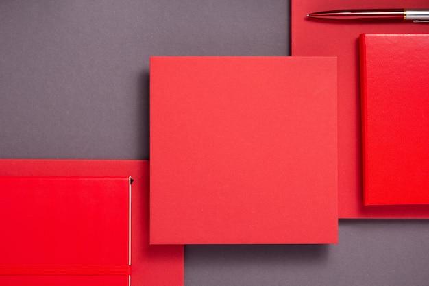 Notizbuch und stift in abstraktem grau mit rotem hintergrund, minimalistischer konzeptstil