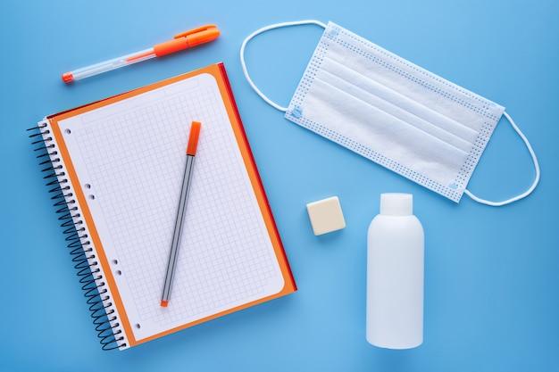 Notizbuch und stift mit einer maske auf blauem hintergrund. schulanfangskonzept und schutz vor covid.