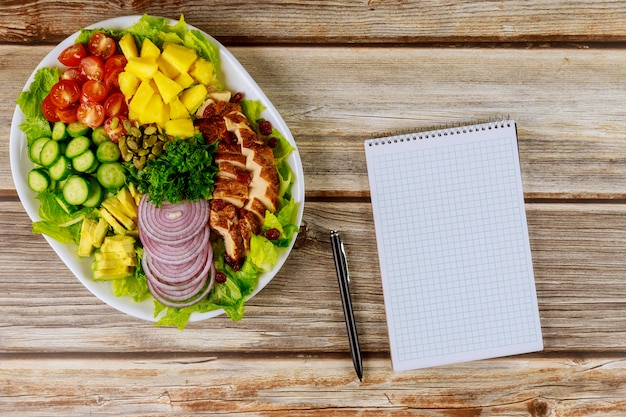 Notizbuch und stift mit gesundem salat auf holztisch