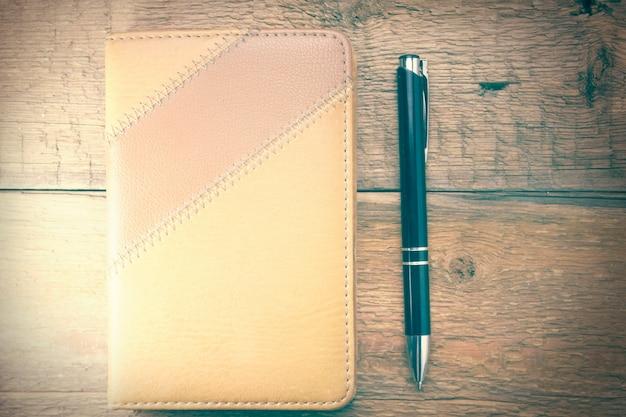 Notizbuch und stift über einem hölzernen hintergrund