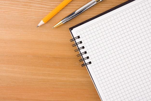 Notizbuch und stifte auf holztisch