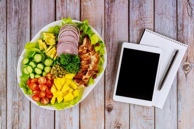 Notizbuch und tablette mit gesundem salat auf holztisch.