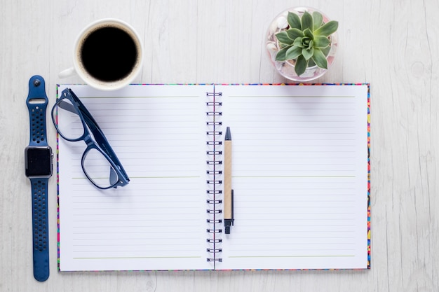 Notizbuch und zubehör in der nähe von kaffee und pflanze
