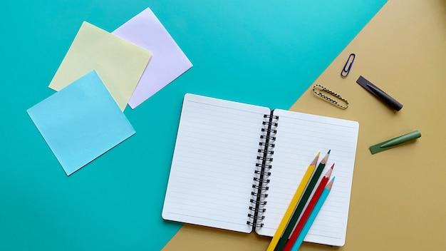 Notizbuch von oben mit buntstiften, büroklammern und bleistiftkappen auf grünem und gelbem hintergrund
